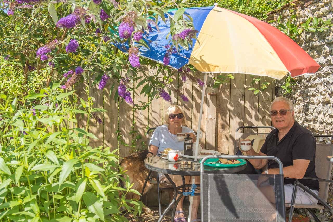 Two customers enjoy a cup of tea and a scone in the sun
