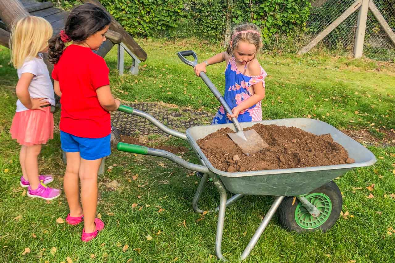 Cleo and friend encouraging Esme as she unloads the wheelbarrow
