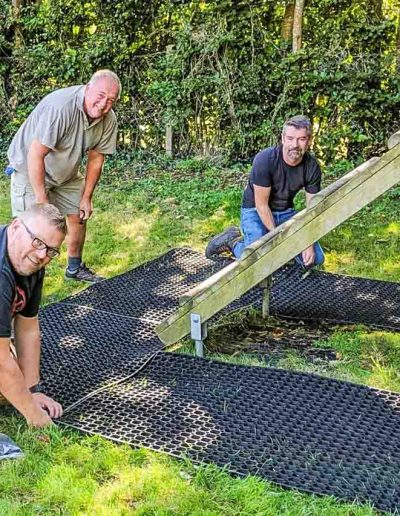 James, Wayne and Adam lay new safety matting for the Obstacle Course