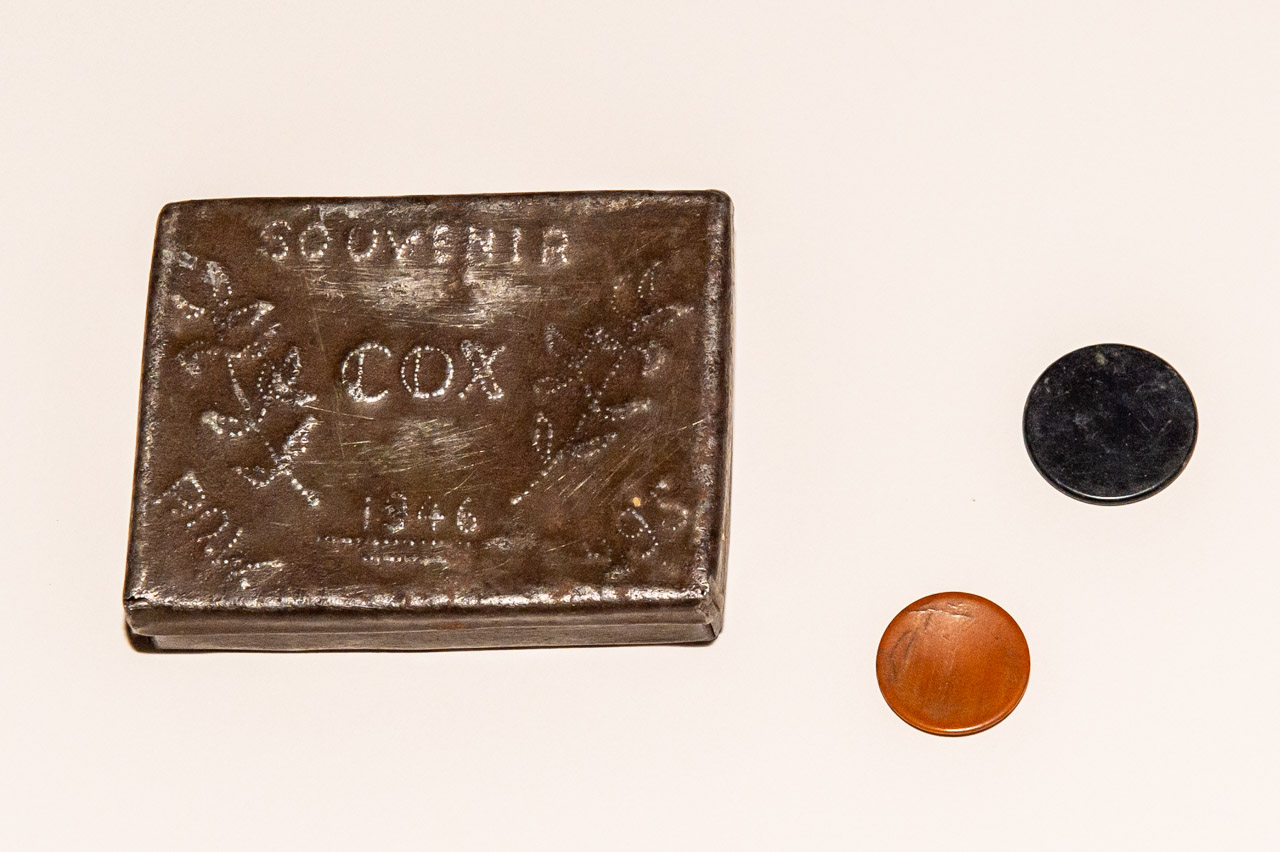 A Cigarette case made by a POW, alongside POW camp currency