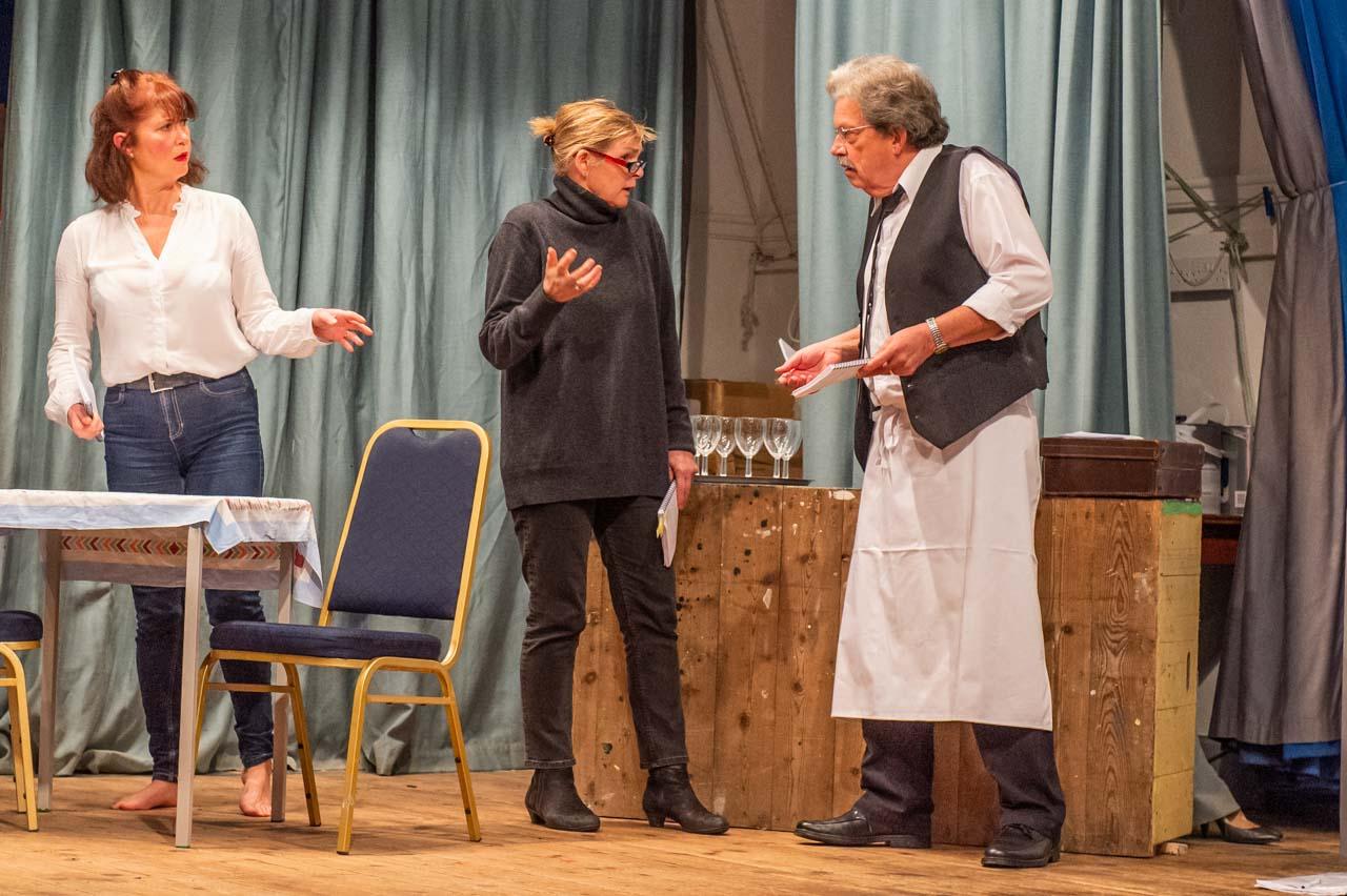 LeClerk explains the latest plot to René, while Yvette listens in