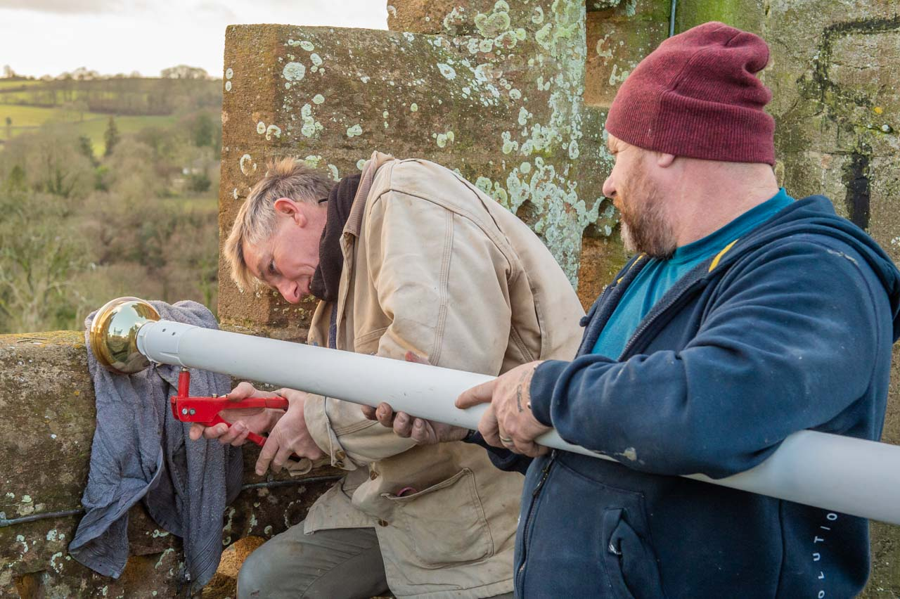 Simon riveting the finial collar to the flagpole, while Nick holds the pole steady