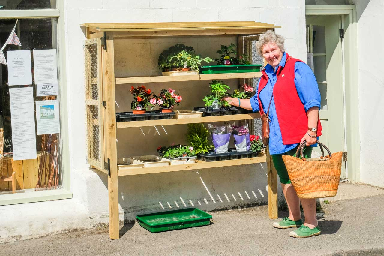 Merrily selecting a plant from Andy and Donna's new plant display stand - designed, built, assembled and installed by Phil
