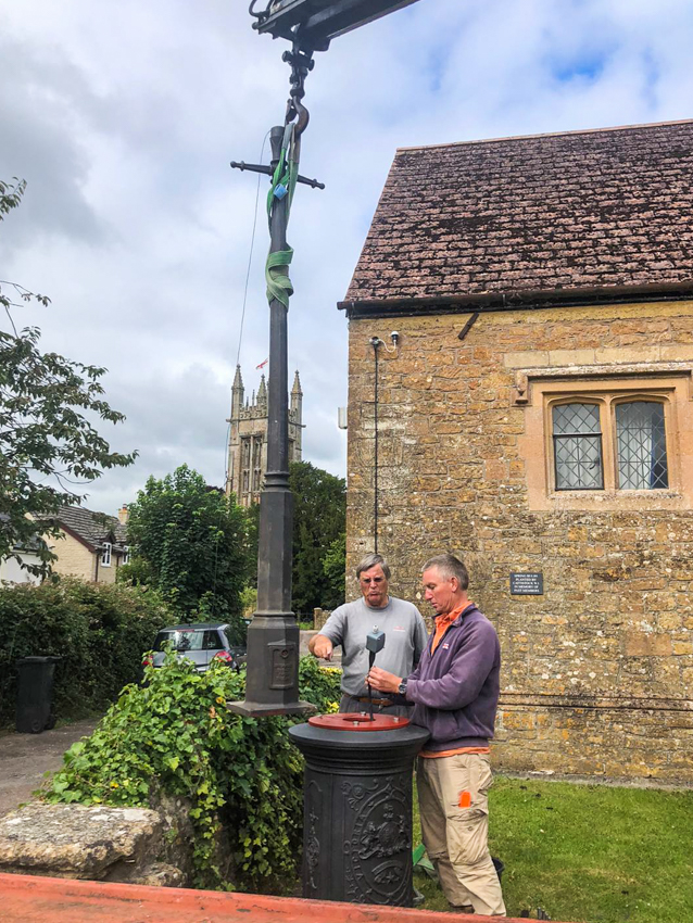 Peter and Simon preparing to connect the electrics as the lamp is lowered onto its base