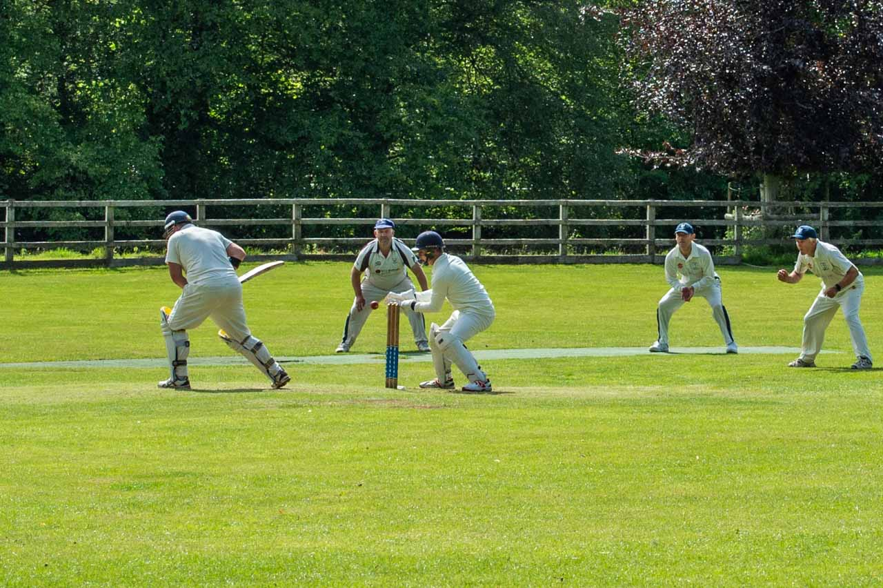The wicketkeeper Leo takes the ball, watched by Ben, Jason and Nigel