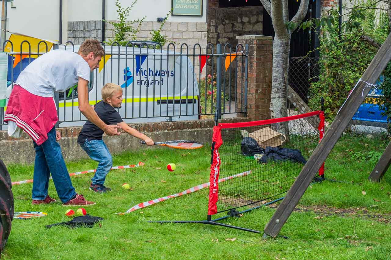 With Dad's help a youngster tries his hand at the tennis game